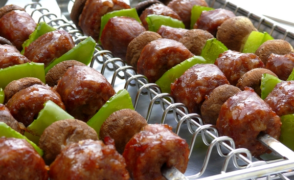 Rows of sausage kabobs sitting in a kabob grilling baket.