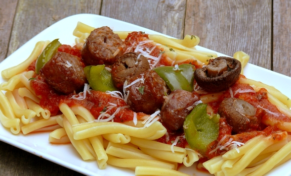 Sausage kabobs sitting on top of pasta.