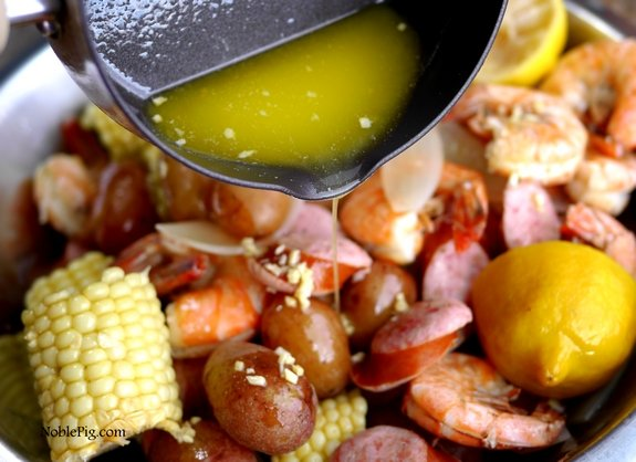 Pouring butter into the finished shrimp boil.