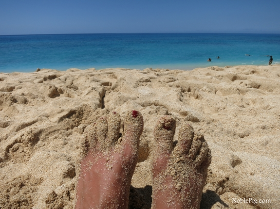 Feet covered in sand on a beach.