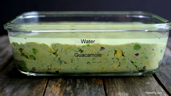 Guacamole in a bowl with water covering it.