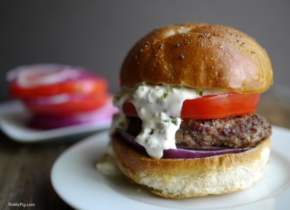 The Juciest Mediterranean Style Burgers with Creamy Feta Curry Dressing on a white plate with tomato and onion in the background.
