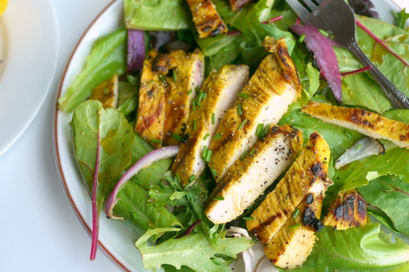 Grilled Turmeric Lemon and Lime Chicken on a bed of lettuce is a great summertime meal