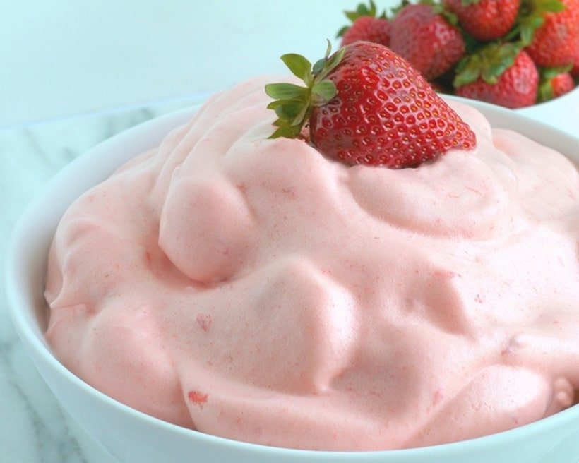 Bowl of strawberry mousse with strawberries on top.