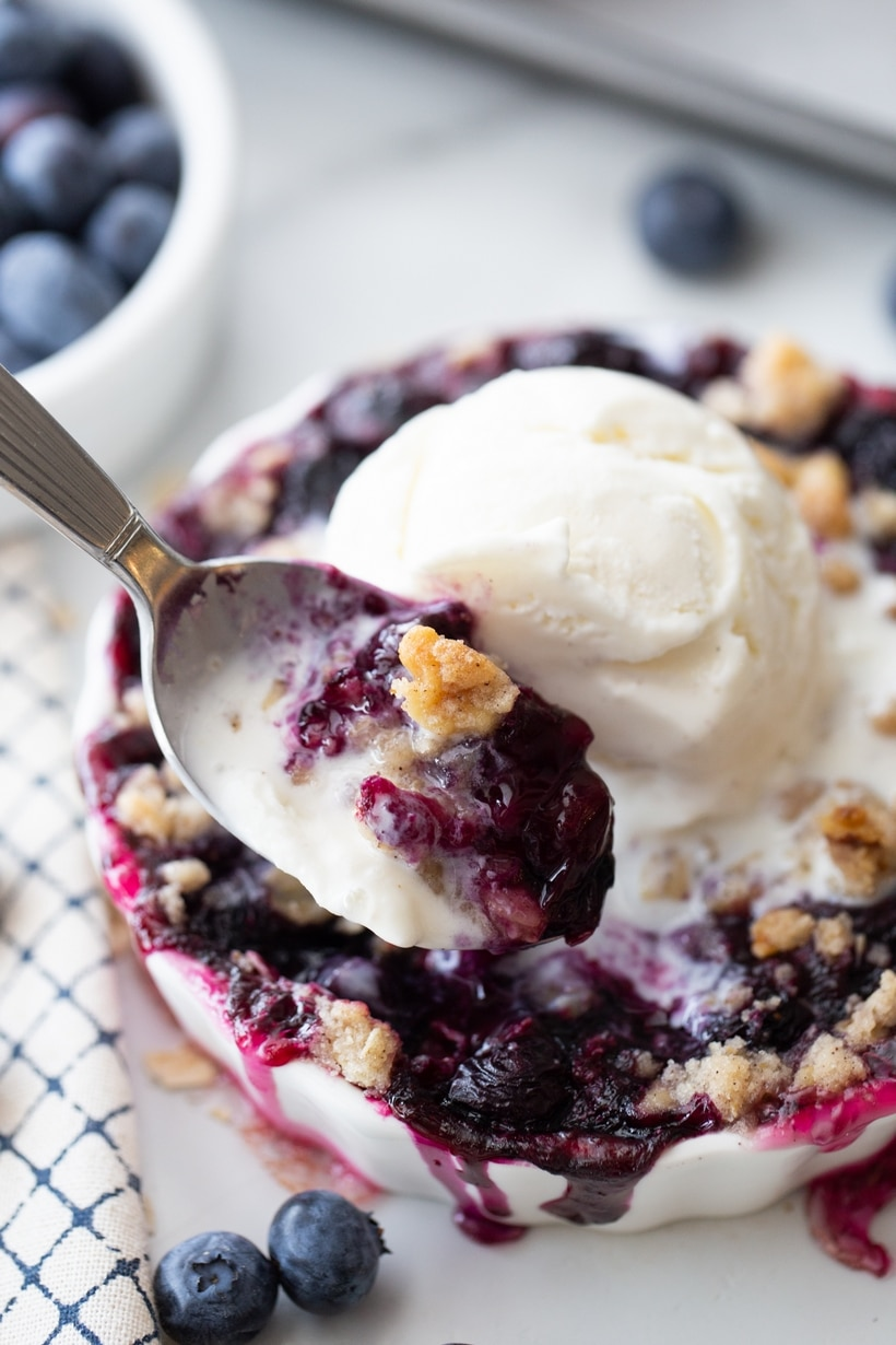 Spoon with blueberry crisp in the background.