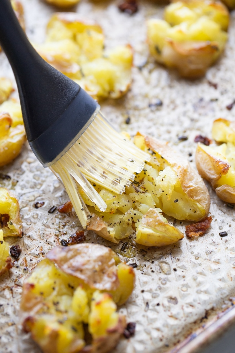 Smashed potatoes being brushed with vinegar.