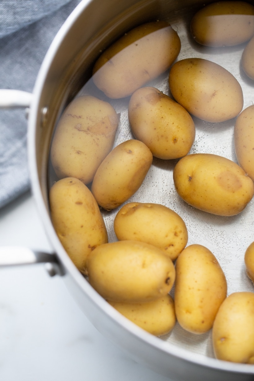 Raw potatoes in a pan of water.