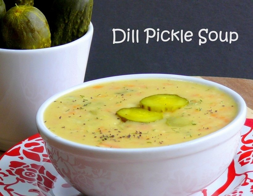 Dill pickle soup in a white bowl with more pickles in the background. The words dill pickle soup appear in the image.