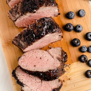 Sliced pork tenderloin with blueberries on the side.