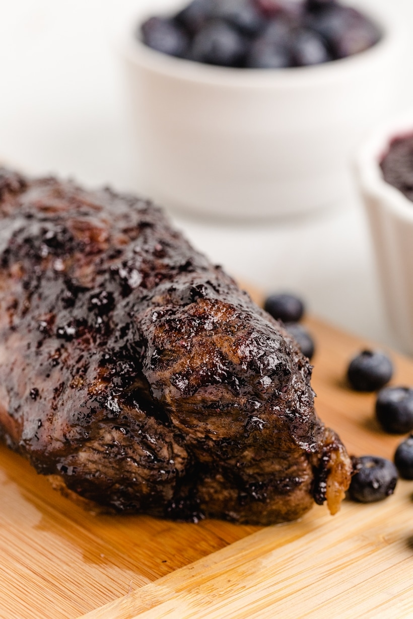 Pork tenderloin with a bowl of blueberries in the background.
