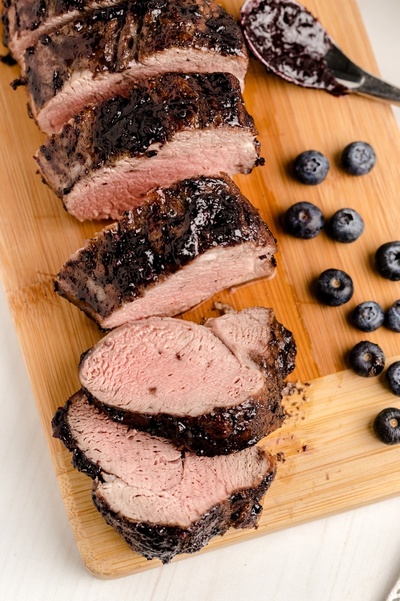 Sliced pork tenderloin with several blueberries on the side on a cutting board.
