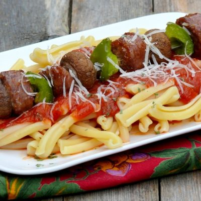 Sausage kabob sitting on top of pasta.