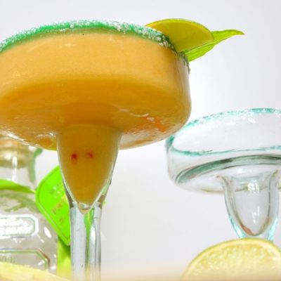 Nectarine margarita in a glass with an empty glass.