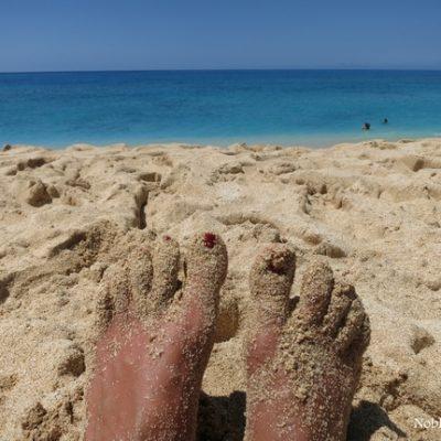 Sandy feet on the beach in Hawaii.
