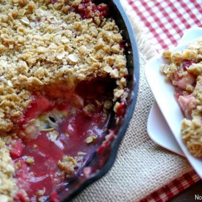 Strawberry Banana Crumble in a cast iron pan and a serving on a white plate.