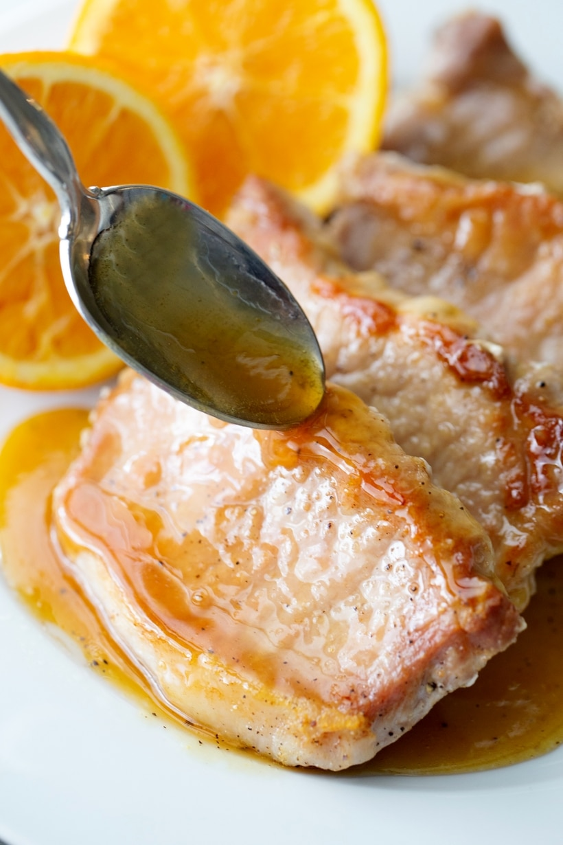 Pork chops with glaze being spooned over them.