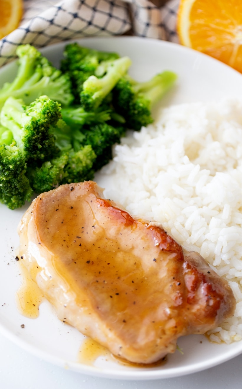 Glaed pork chop sitting on a plate with rice and broccoli.