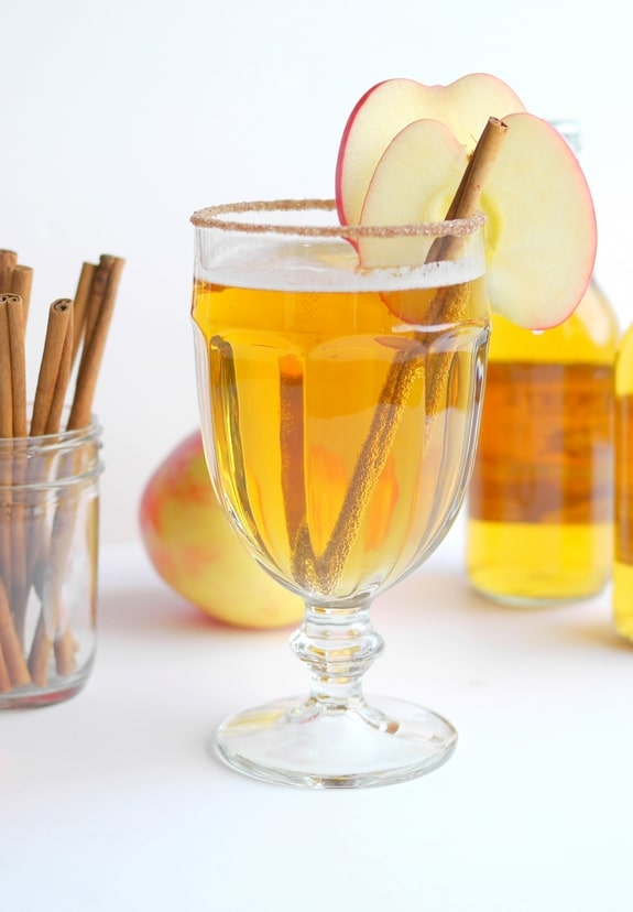 Beer cider slam in a tall glass with a cinnamon stick and slice of apple. Bottle of cider in the background along with cinnamon sticks in a jar.
