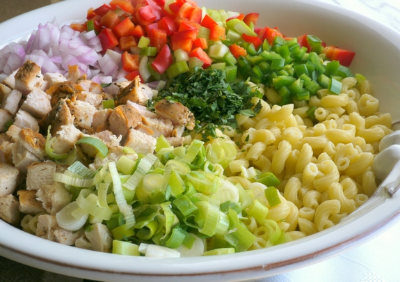 Macaroni salad ingredients together in a bowl before being mixed.