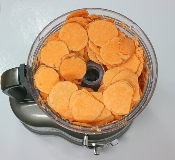 Sliced sweet potatoes sitting in the bowl of a food processor.