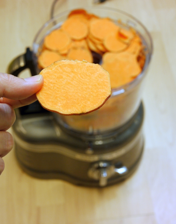 Sliced sweet potato being held by a hand with more in a food processor in the background.