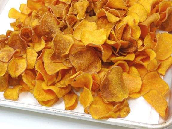 A pile of the Best Homemade Sweet Potato Chips on a baking tray.