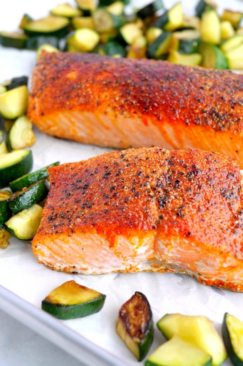 Two pieces of cooked salmon surrounded by veggies.