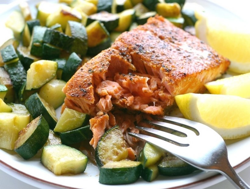 Flaked salmon on a bed of zucchini with lemon slices and a fork.