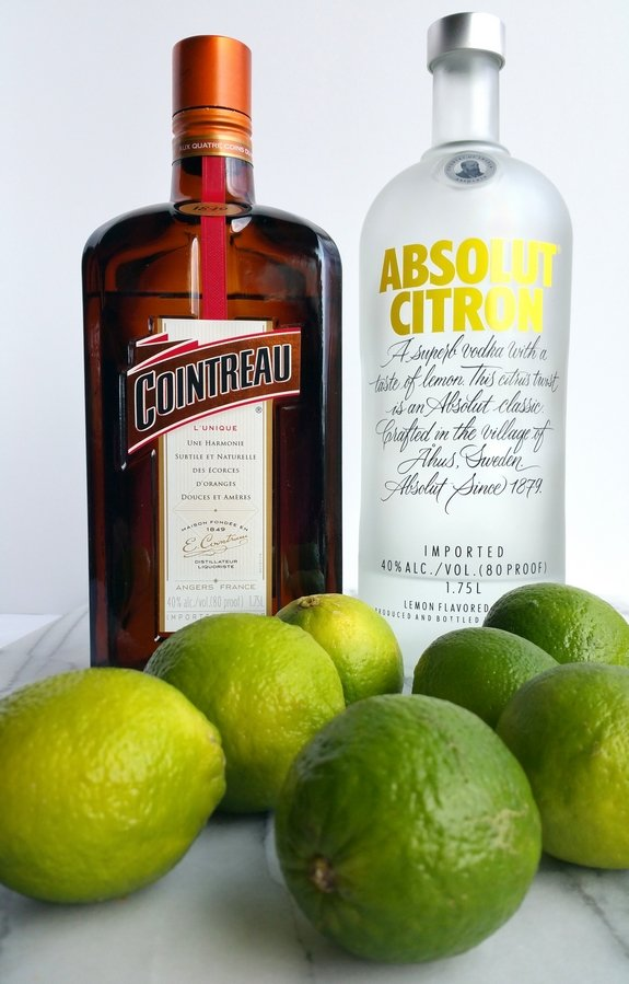 Bottle of Cointreau and Absolut Citron vodka with limes.