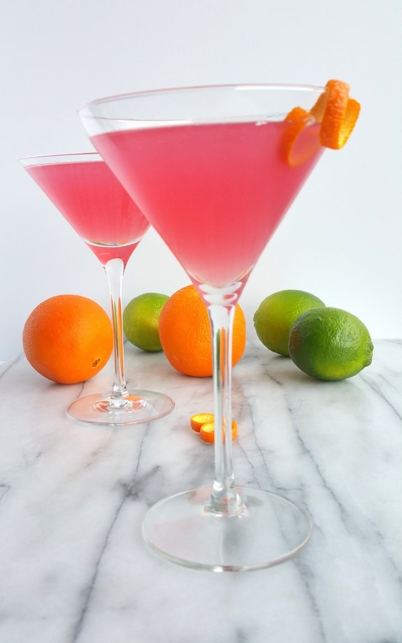 World's Best Cosmopolitan Cocktail in martini glasses with limes and oranges in the background.