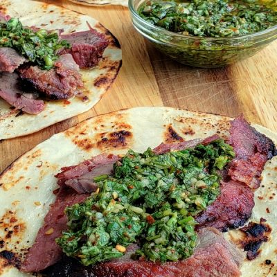 Flank steaks tacos, three of them, with bowl of chimichurri.