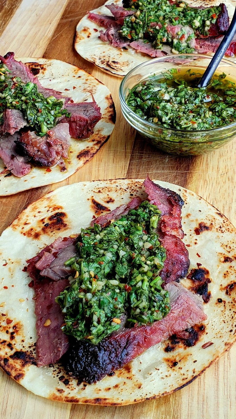 Three Flank Steak Tacos with Garlicky Cilantro Chimichurri with a bowl of chimichurri.