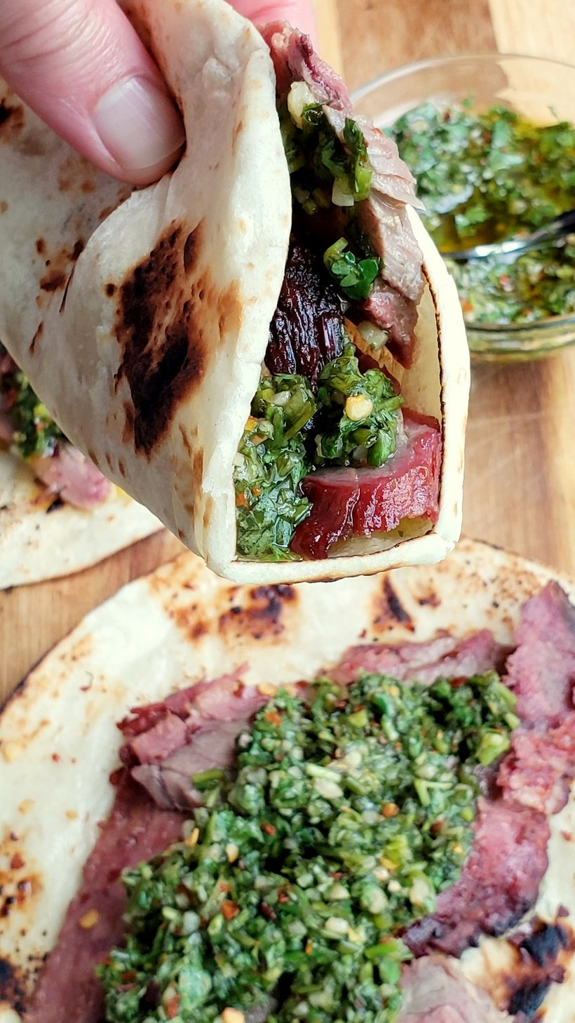 Hand holding a flank steak taco with one below..bowl of chimichurri in the background.