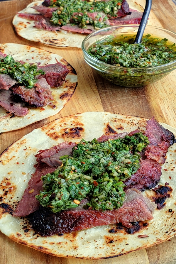 Make the best street food at home with these Flank Steak Tacos with Garlicky Cilantro Chimichurri. These tacos are essentially going to be your go-to summer, grilling meal. #noblepig #grilling #beef #flanksteak #chimichurri