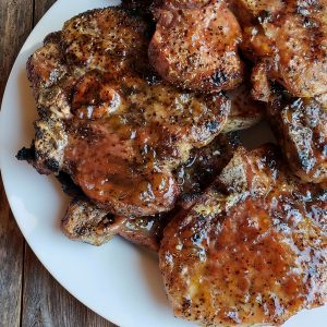Grilling a quick and easy meal has never been so easy. These tender and Juicy Grilled Pork Chops with Spicy Peach Glaze come together quickly for a dinner your family and friends will not soon forget. The glaze can be put together in minutes, while the pork chops undergo a quick brine. #noblepig #pork #porkchops #grilling #easydinners