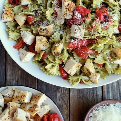 Chicken pesto pasta in a white bowl with grated Parmesan and a bowl of chicken and red peppers.