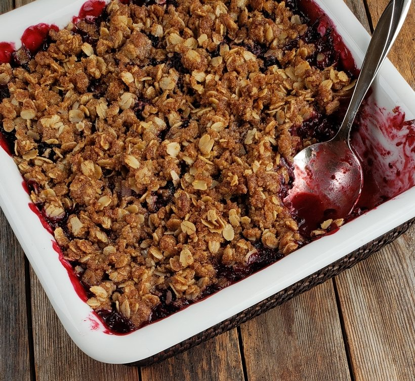 Baked Blackberry Crumble with a spoon in a serving dish.