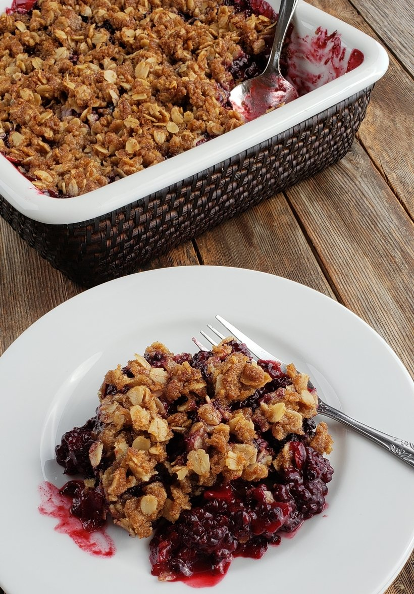 A serving of blackberry crumble on a white plate with serving dish in the background.