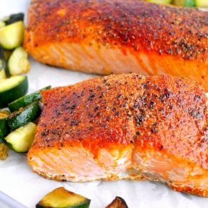 Two pieces of air fryer salmon surrounded by veggies.
