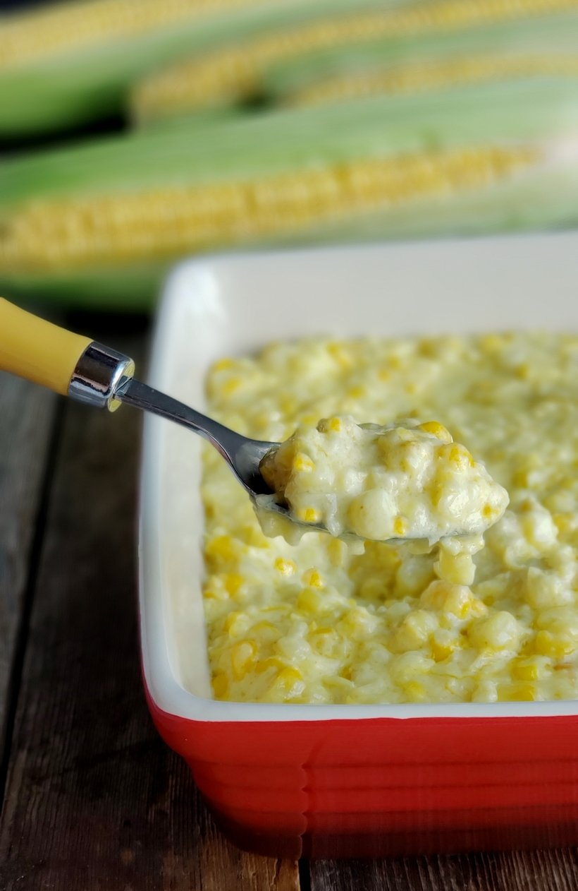 Creamed corn in a red serving dish with a spoon scooping some out.