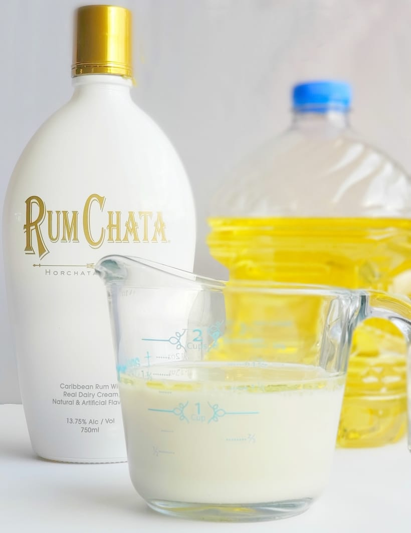 Bottle of RumChata liqueur and measured out in a measuring cup. Bottle of cooking oil in the background.