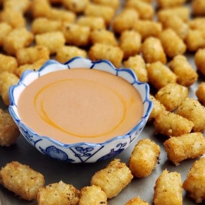 Tater tots surrounding a bowl of sauce on a tray.