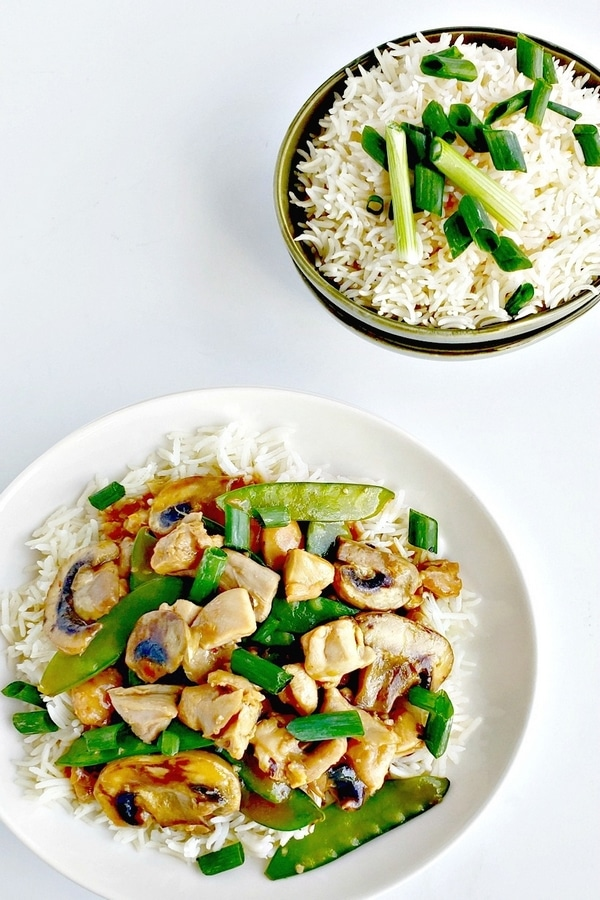 Chicken and snow pea stir-fry on a white plate.