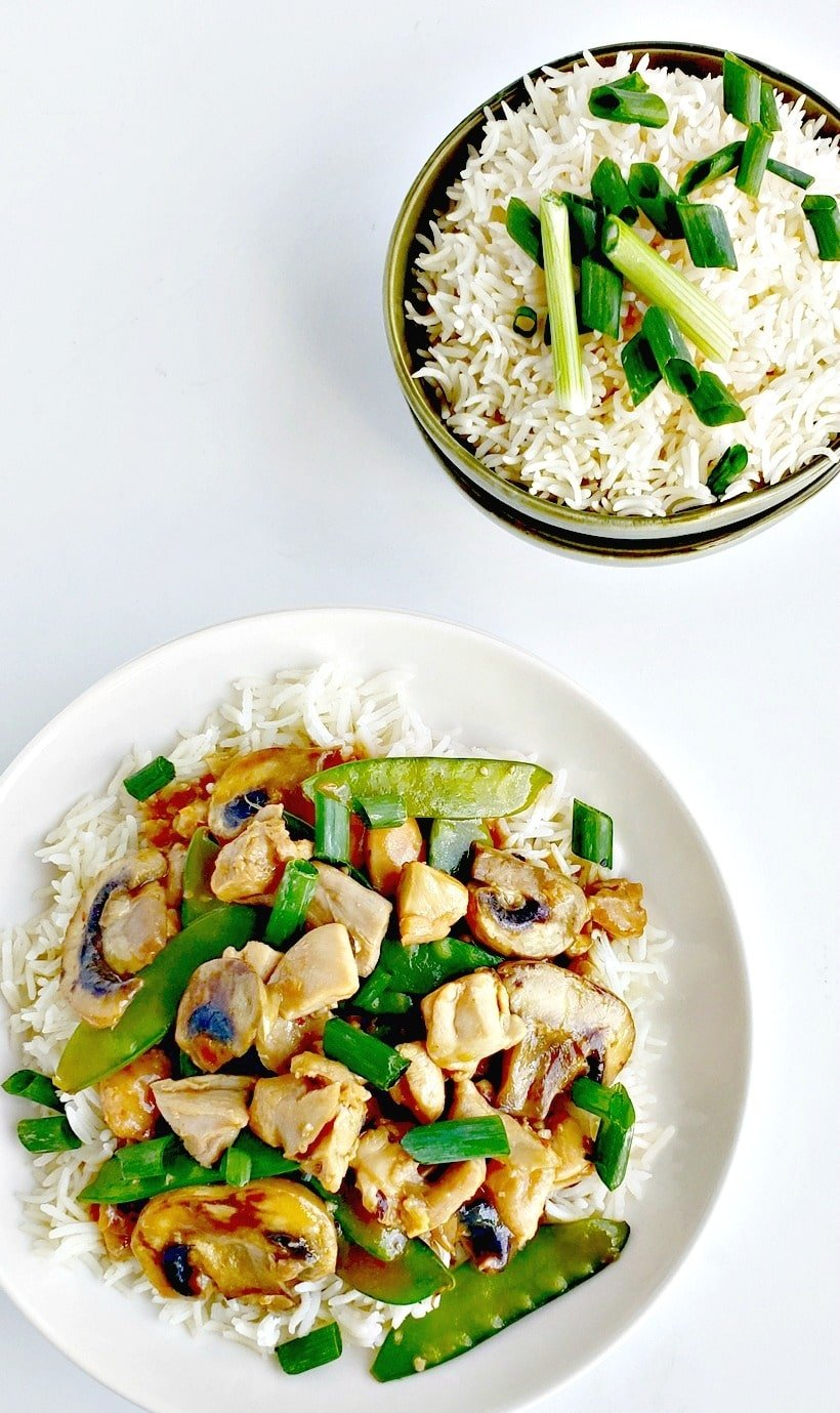 Chicken and snow pea stir-fry on a plate and a bowl of rice.