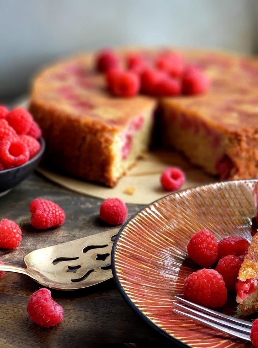Cake with a slice missing surrounded by raspberries.