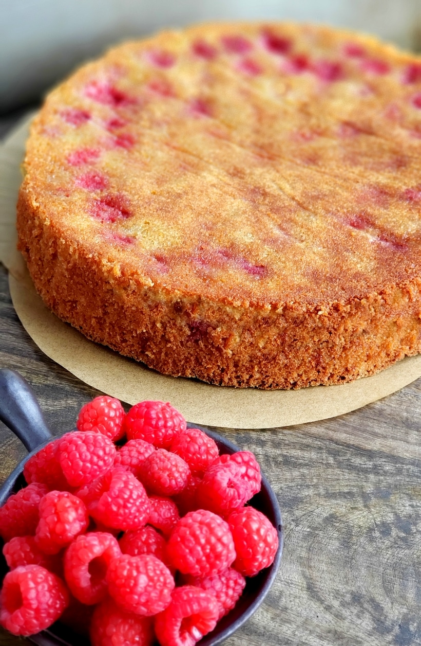 Fresh raspberries in a bowl and a the whole cake in the background.