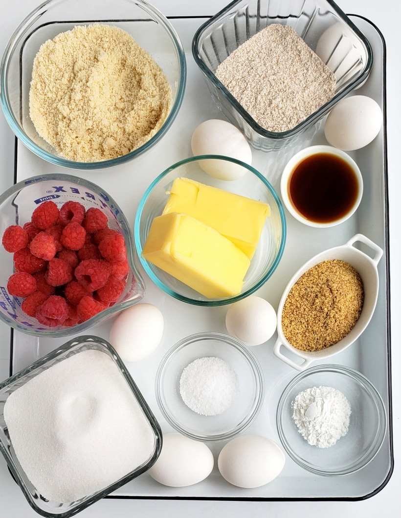 A tray of ingredients for healthier raspberry cake all in different bowls.