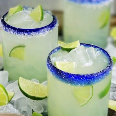 Three glasses with agave margaritas surrounded by ice and lime.