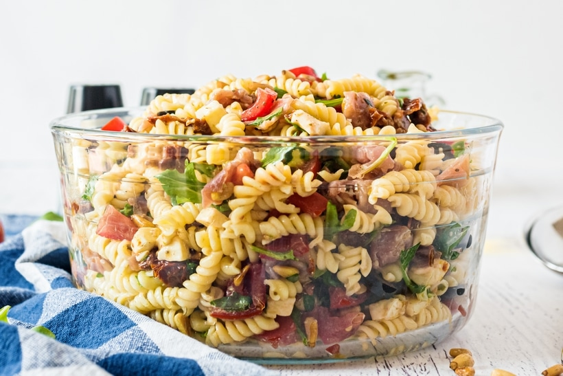 Frontal view of Italian pasta salad in a clear bowl.